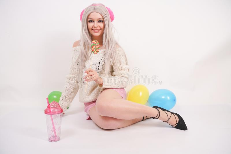 Cute blonde caucasian happy girl dressed in a milky color knitted sweater and funny shorts, she sits on the white floor alone with stock images