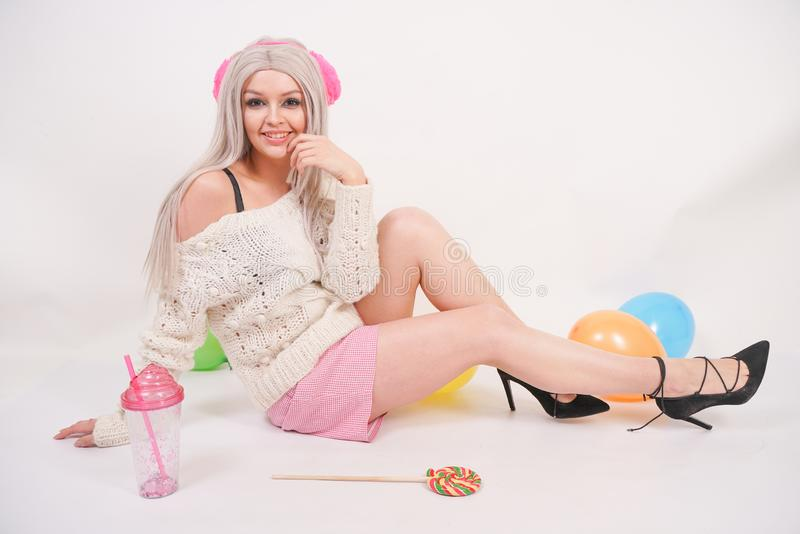Cute blonde caucasian happy girl dressed in a milky color knitted sweater and funny shorts, she sits on the white floor alone with. Balloons and a glass of royalty free stock image