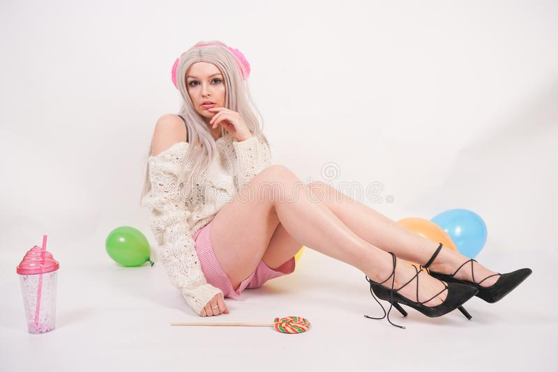 Cute blonde caucasian happy girl dressed in a milky color knitted sweater and funny shorts, she sits on the white floor alone with. Balloons and a glass of stock photo