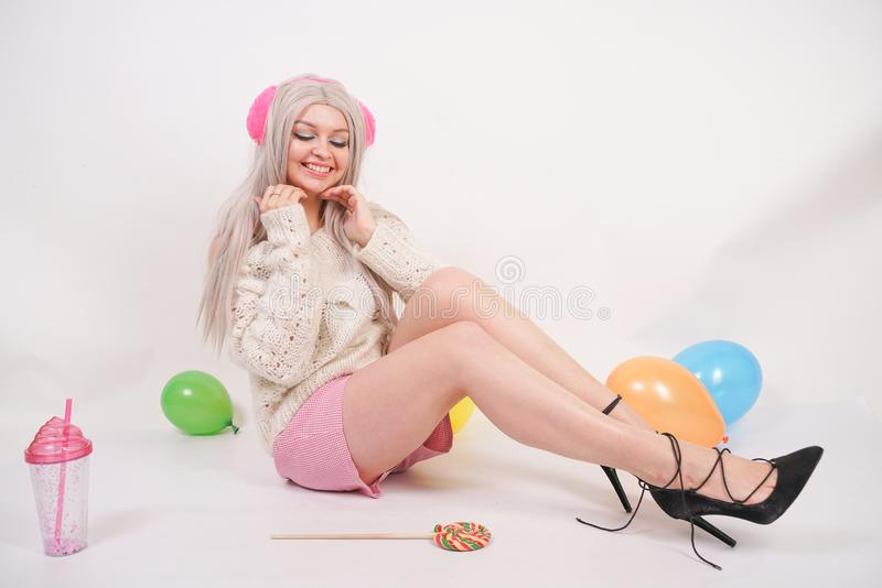 Cute blonde caucasian happy girl dressed in a milky color knitted sweater and funny shorts, she sits on the white floor alone with. Balloons and a glass of royalty free stock images