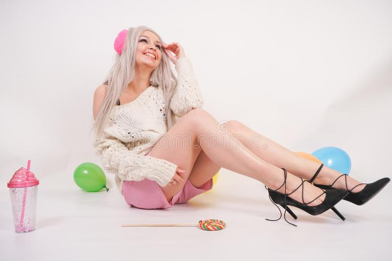 Cute blonde caucasian happy girl dressed in a milky color knitted sweater and funny shorts, she sits on the white floor alone with. Balloons and a glass of stock photos