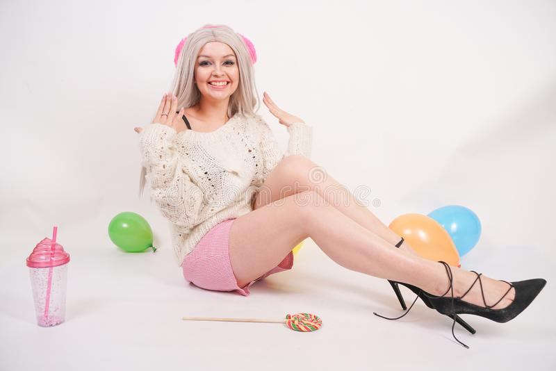 Cute blonde caucasian happy girl dressed in a milky color knitted sweater and funny shorts, she sits on the white floor alone with stock photo