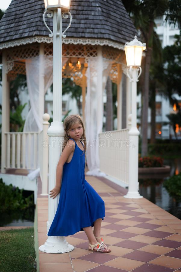 Cute blonde Caucasian little girl in blue dress leans against a pillar . Evening scene with gazebo is on the background. stock photography