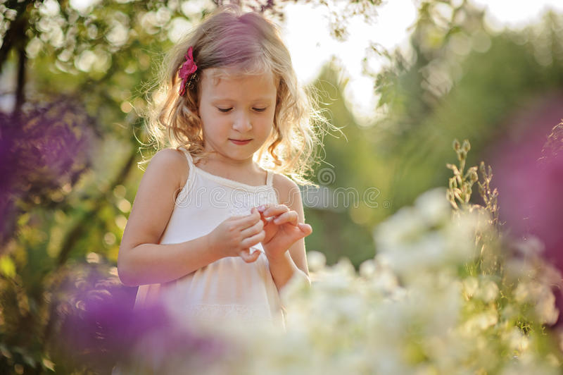 Cute blonde child girl in blooming summer garden stock photo