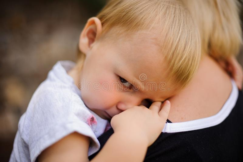 Cute blonde child lying on mom`s shoulder royalty free stock photo