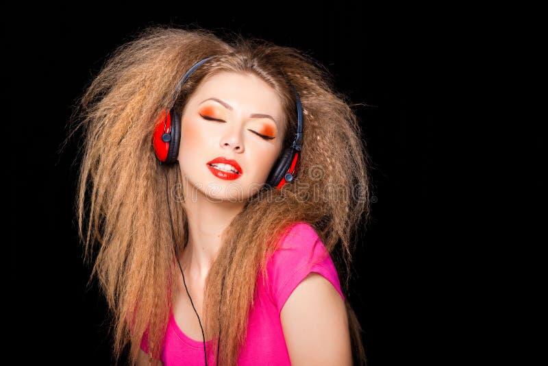 Cute blonde girl listening music on big headphones