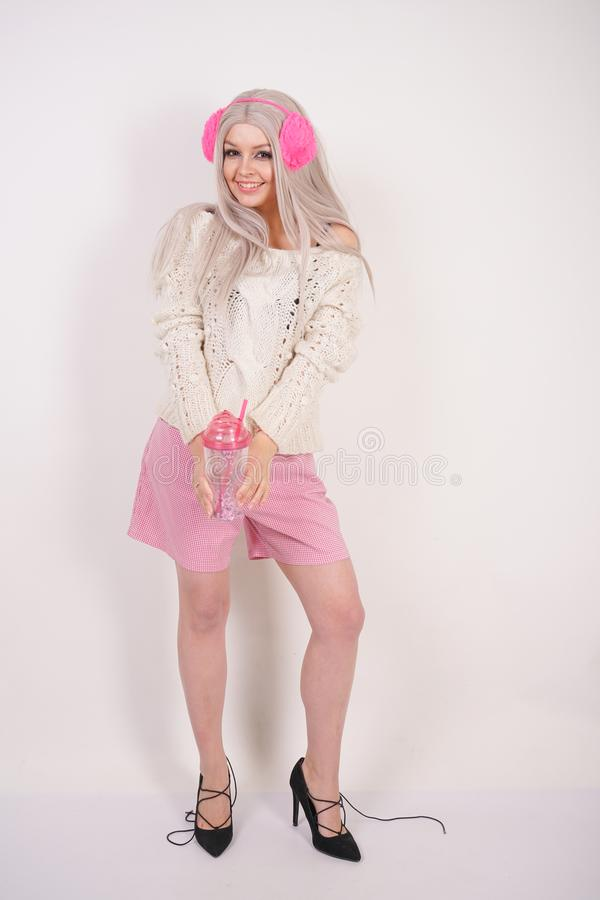 Cute blonde girl stands in fashionable casual bright clothes and drinks water from a pink transparent glass cup with sequins on wh. Ite studio background stock photo
