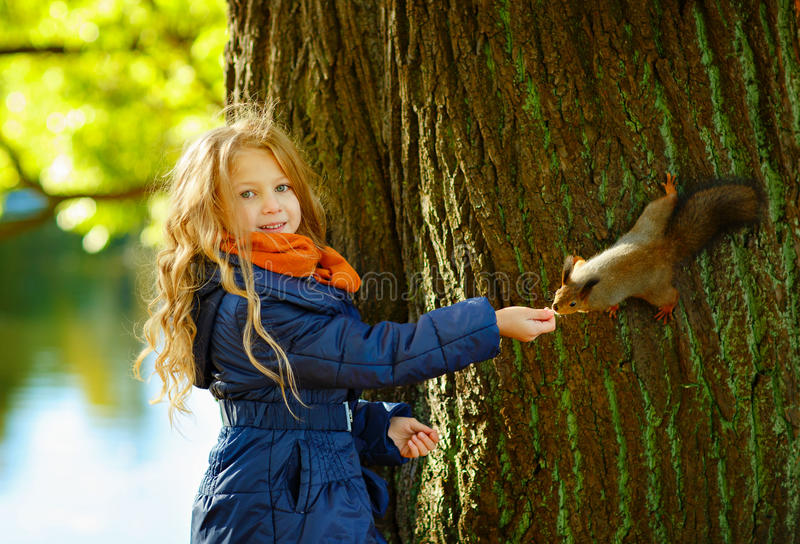 A cute blonde girl 6 years old smiling and feeding a squirrel in stock image