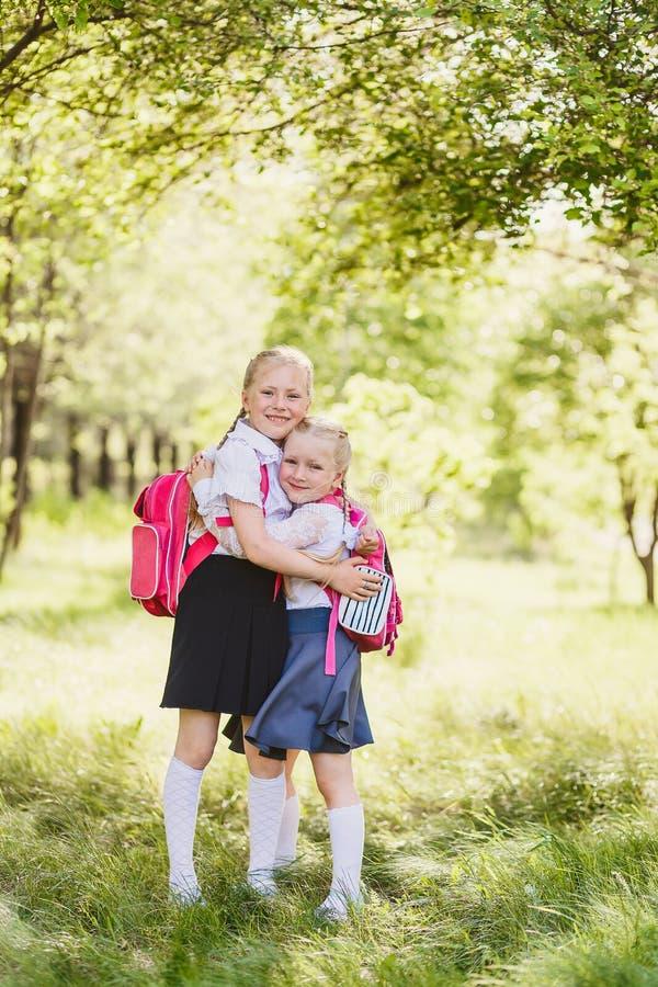 Cute blonde girls in school uniform hugging outdoors royalty free stock image