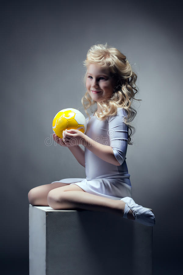 Cute blonde gymnast posing with ball on cube. Close-up stock photo