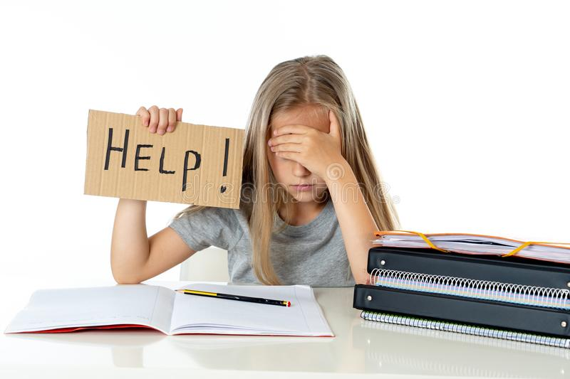Cute blonde hair school girl holding a help sign in a education concept stock photography