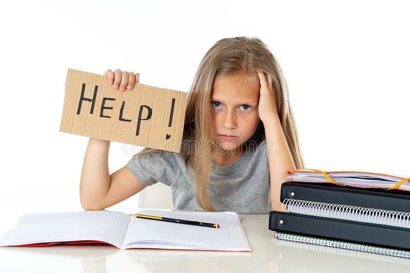 Cute blonde hair school girl holding a help sign in a education concept royalty free stock images