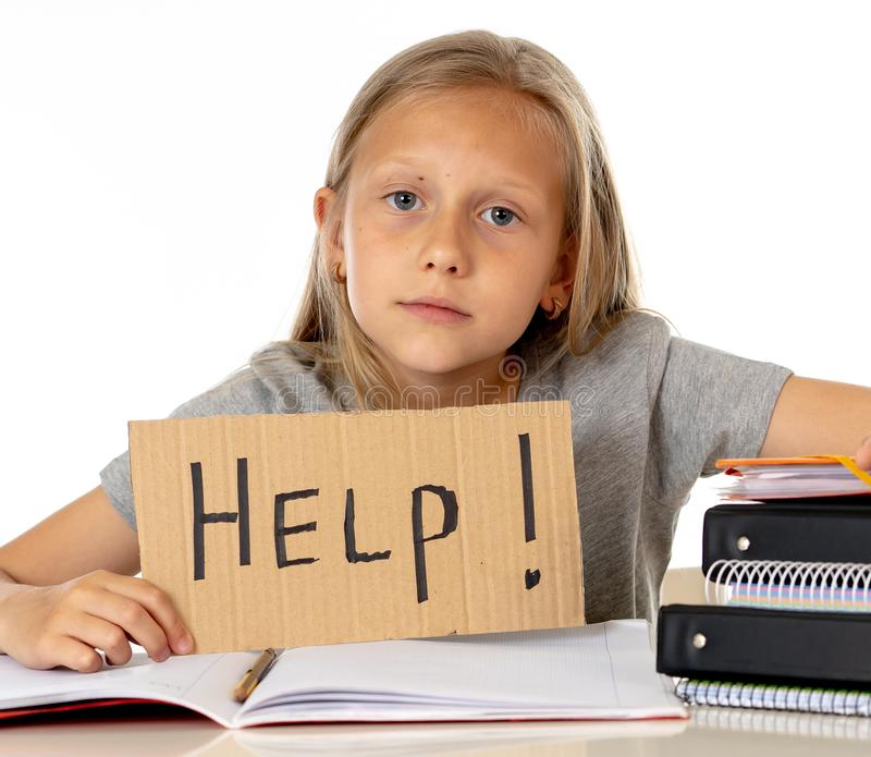 Cute blonde hair school girl holding a help sign in a education stock photos