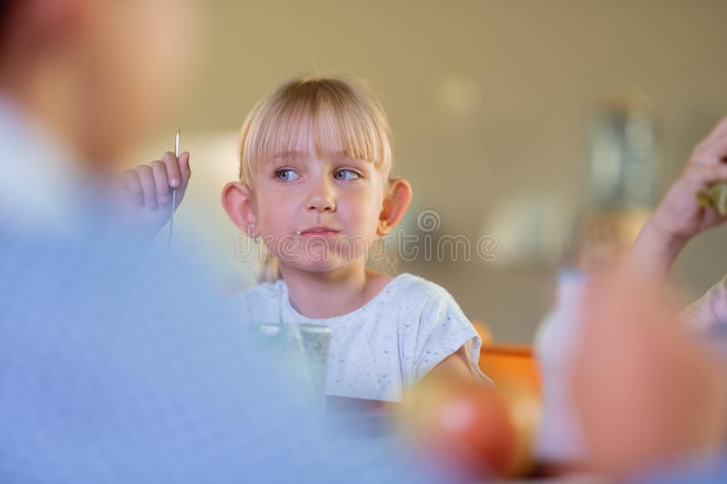 Cute blonde-haired schoolgirl having lunch with classmates royalty free stock photos