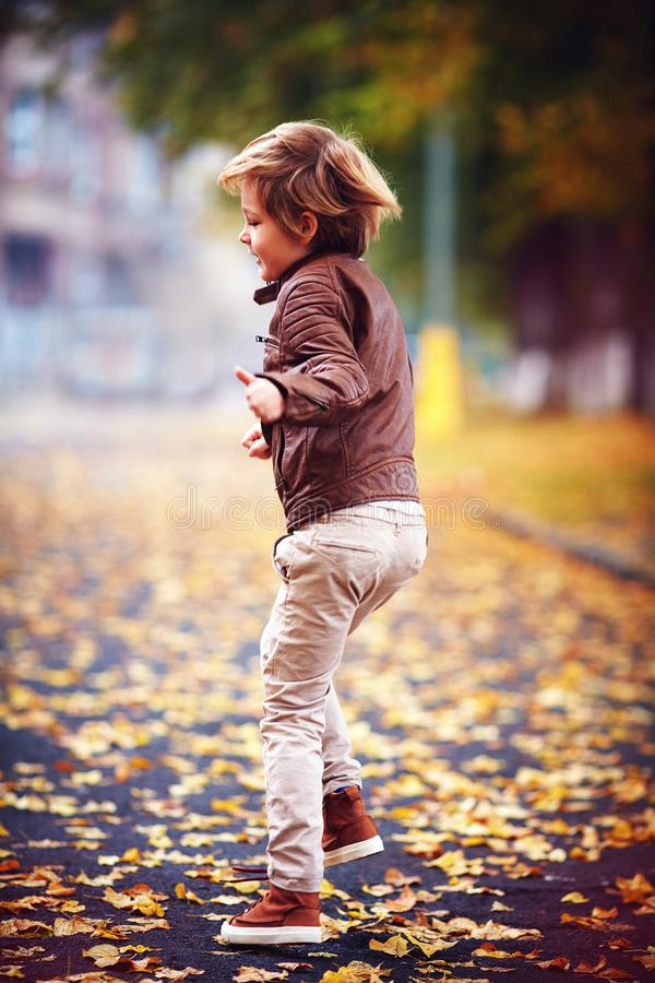 Cute kid, boy in leather jacket having fun at autumn street, jumping and running around on carpet of fallen leaves royalty free stock image