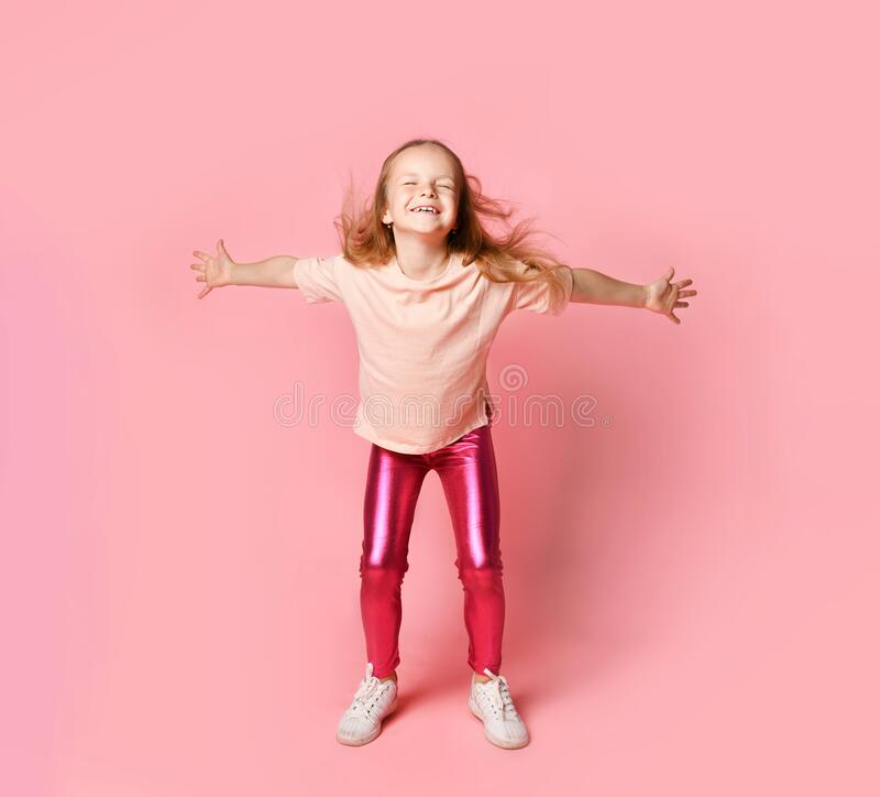 Cute blonde kid in t-shirt and leggings. She smiling and dancing , posing on pink studio background. Close up royalty free stock photography