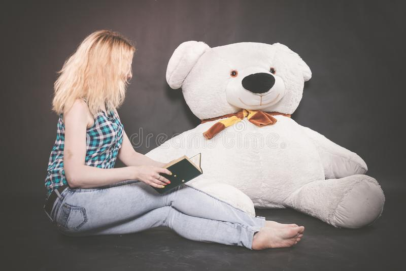 Cute blonde teen in jeans and plaid shirt plays with her huge Teddy polar bear in yellow scarf on black background royalty free stock image