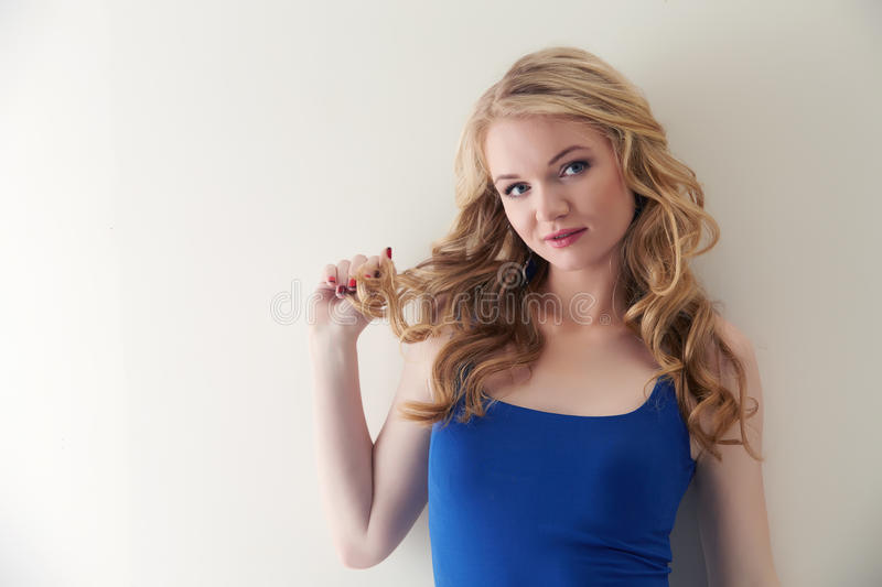 Cute blonde twists her hair strand on finger stock image