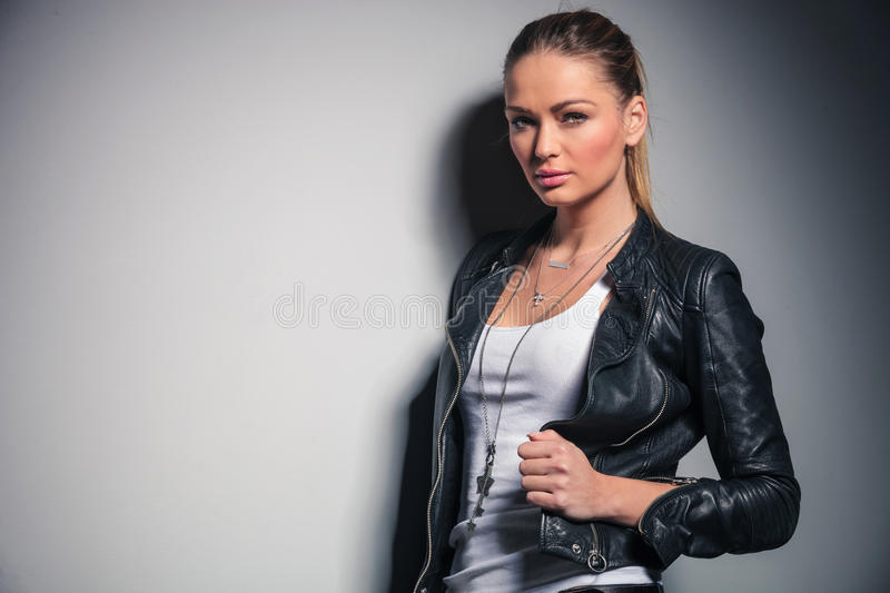 Cute blonde woman in leather jacket holds her collar royalty free stock images