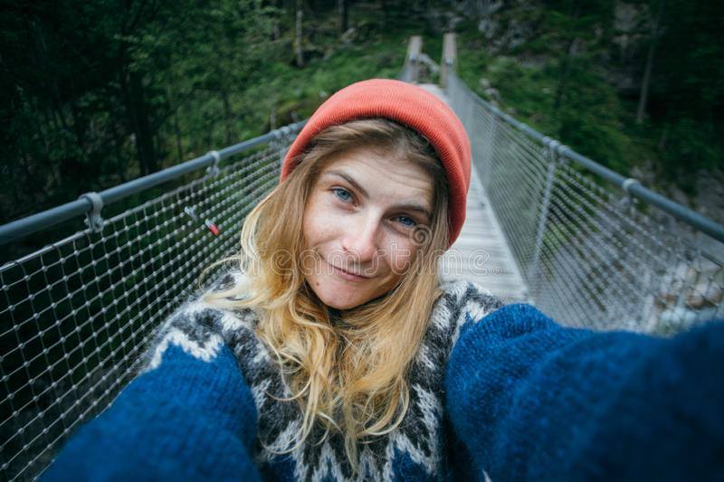 Cute blonde woman makes selfie in forest. Cute and pretty, young girl or woman, adventurer or travel blogger, makes selfie on camera. wears blue wool knit stock photos
