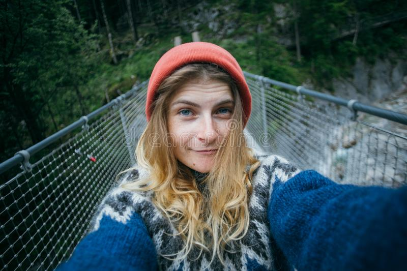 Cute blonde woman makes selfie in forest. Cute and pretty, young girl or woman, adventurer or travel blogger, makes selfie on camera. wears blue wool knit stock photography