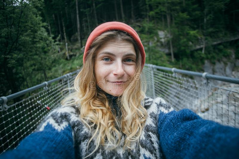 Cute blonde woman makes selfie in forest. Cute and pretty, young girl or woman, adventurer or travel blogger, makes selfie on camera. wears blue wool knit royalty free stock image