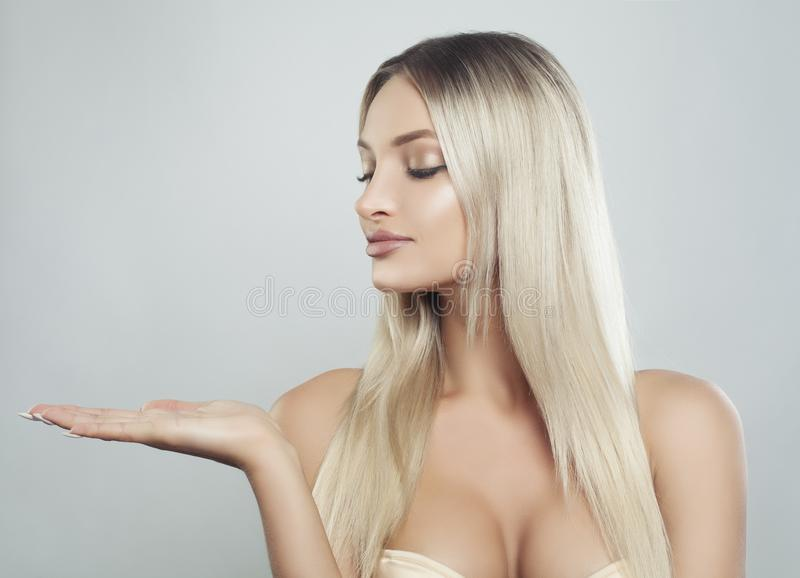 Cute Blonde Woman Spa Model with Healthy Skin. Long Hair and Natural Make up Showing Empty Copy Space on the Open Hand. Product Placement and Advertising stock photography