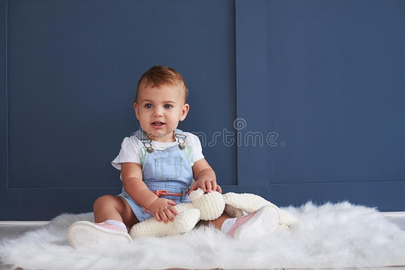 Cute blue-eyed baby girl with toy sitting on the floor stock image