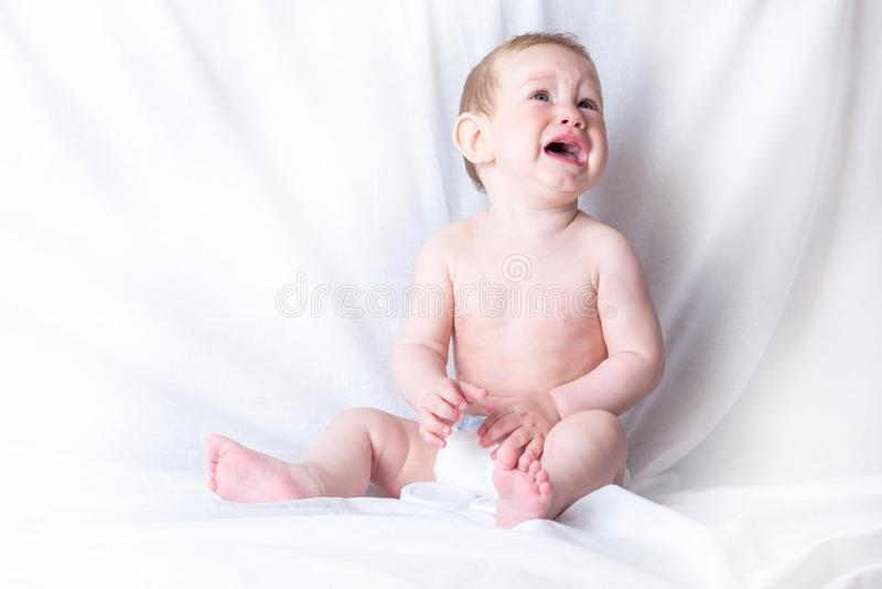 Cute baby 6-9 months old sad crying white background. Children`s emotions. The pain of teething. Cute blue-eyed baby 6-9 months old sad crying white background royalty free stock photography