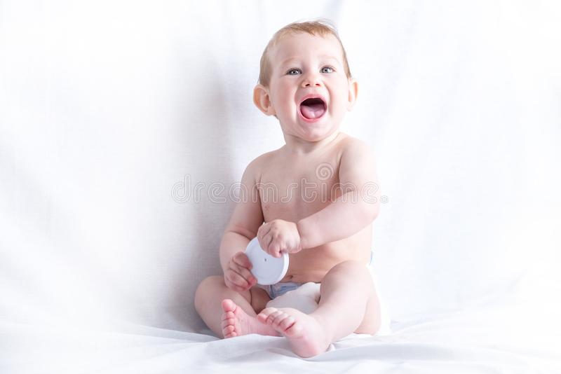 Cute blue-eyed baby 6-9 months smiling and playing on white background. Children`s emotions stock photography