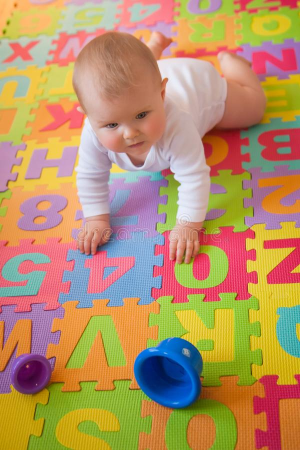 Baby learning to crawl on alphabet mat royalty free stock photography