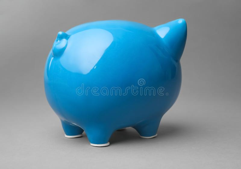 Cute blue piggy bank. On gray background royalty free stock photo