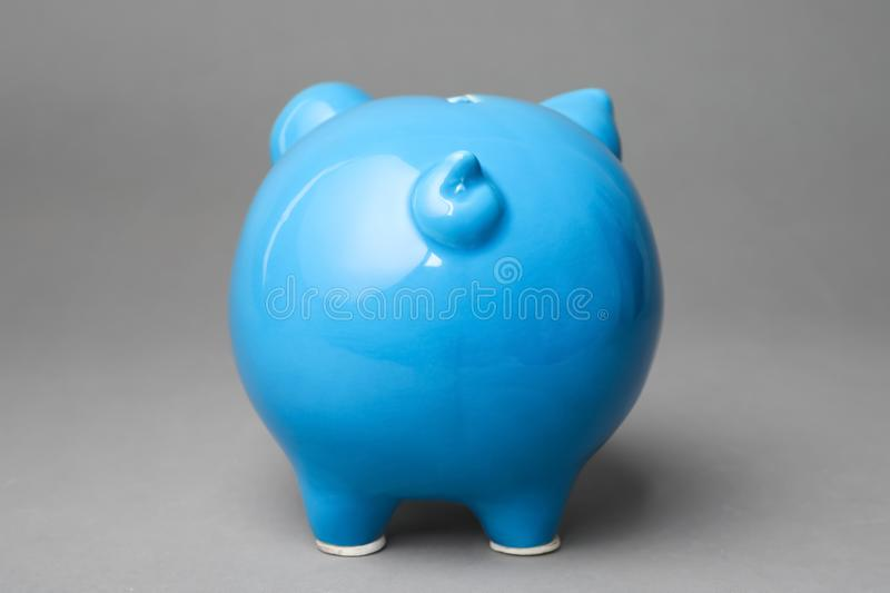 Cute blue piggy bank. On gray background stock photo