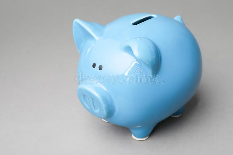 Cute blue piggy bank. On gray background stock photos