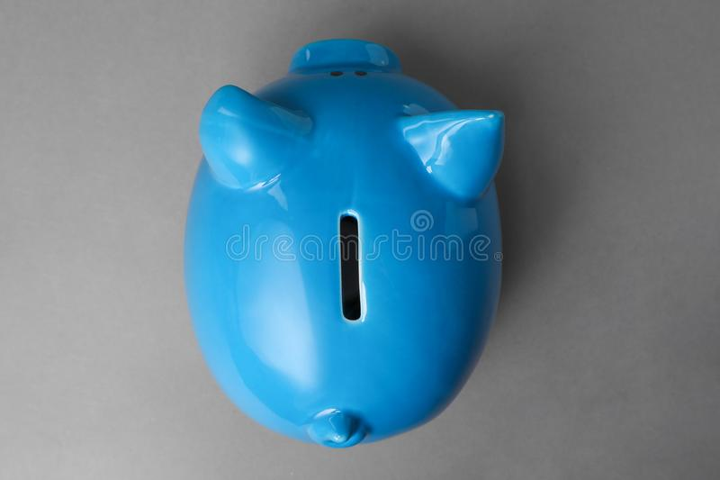 Cute blue piggy bank on gray background. Top view royalty free stock image