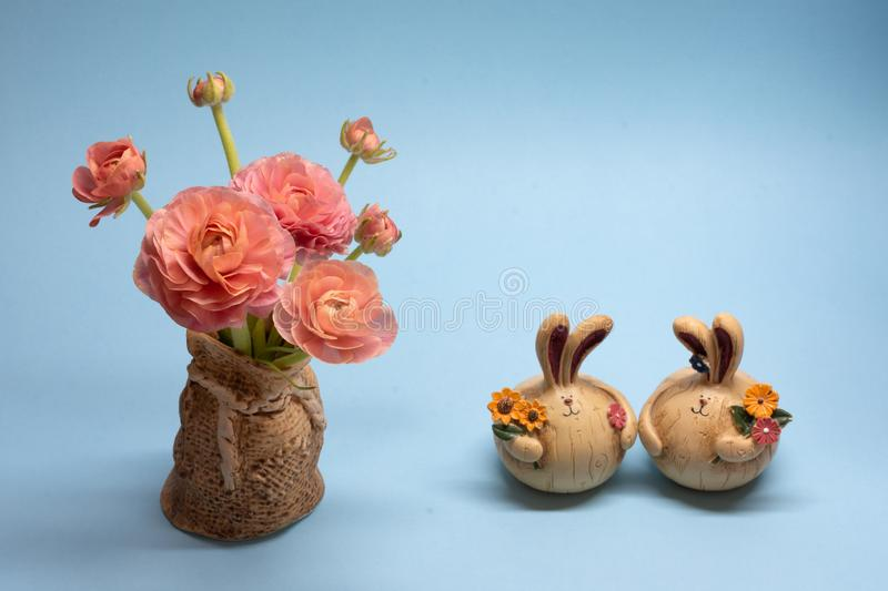 Cute bouquet of delicate pink buttercups and hare figurines on a blue background royalty free stock photos