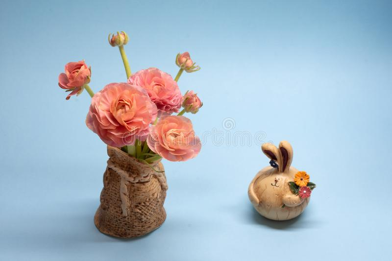 Cute bouquet of delicate pink buttercups and hare figurines on a blue background royalty free stock images