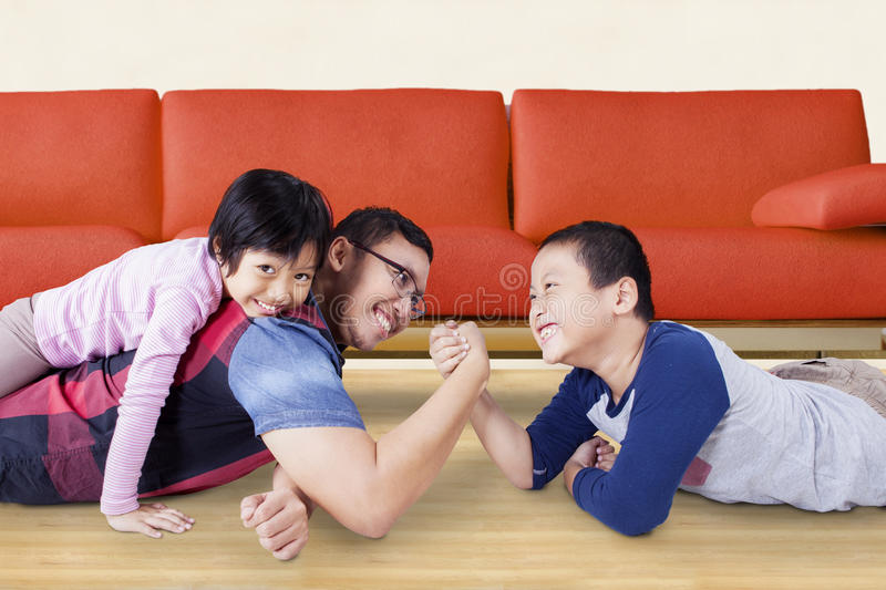 Cute boy arm wrestling with his dad. Portrait of little boy with funny expression while arm wrestling with his father at home stock images