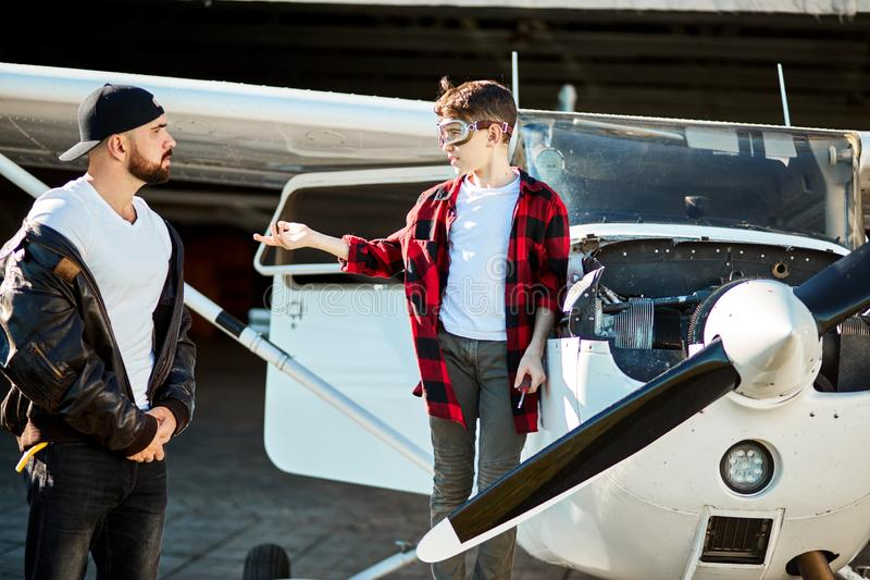Boy in aviator glasses standing near propeller plane asking brother to bring tools stock photos