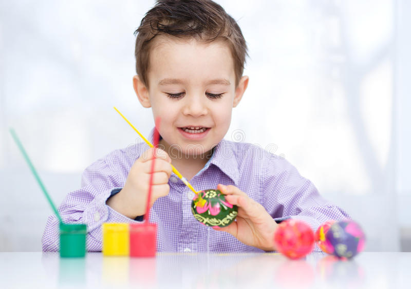 Cute boy with basket full of colorful eggs. Preparing for Easter stock photos