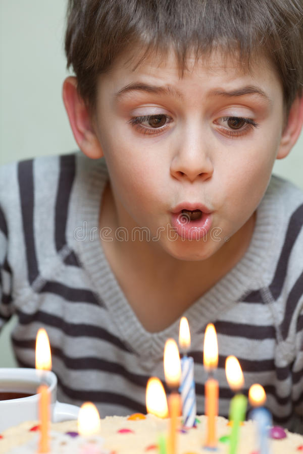 Cute boy at birthday cake royalty free stock image