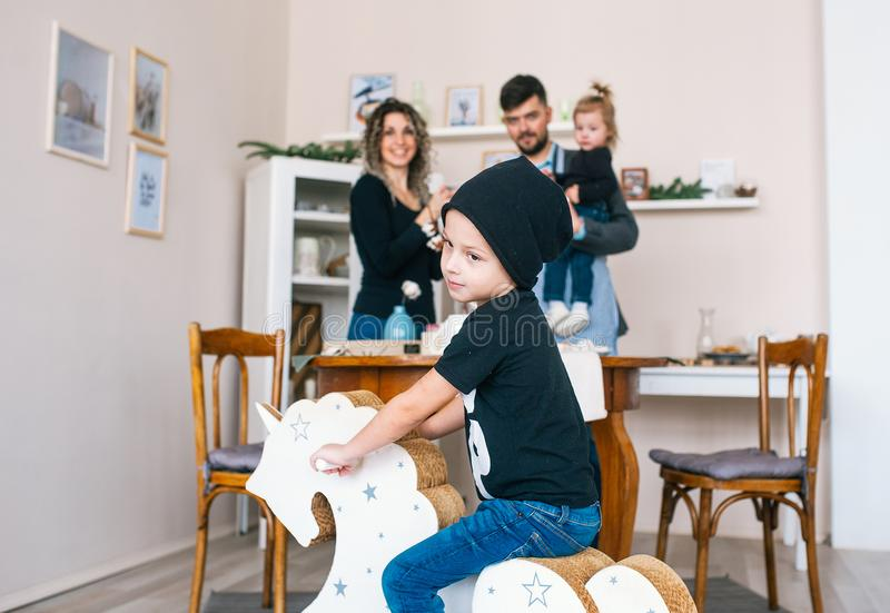 Cute boy in black cap and t-shirt rocking on wooden horse. Little child having fun with pony toy. stock image