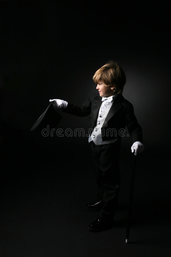 Cute boy in black tuxedo and white gloves royalty free stock photography