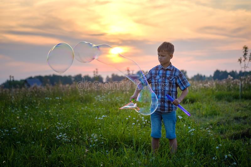 Cute boy blowing big soap bubbles in the meadow royalty free stock photo