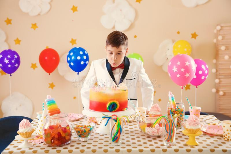 Cute boy blowing out candles on his birthday cake indoors royalty free stock image