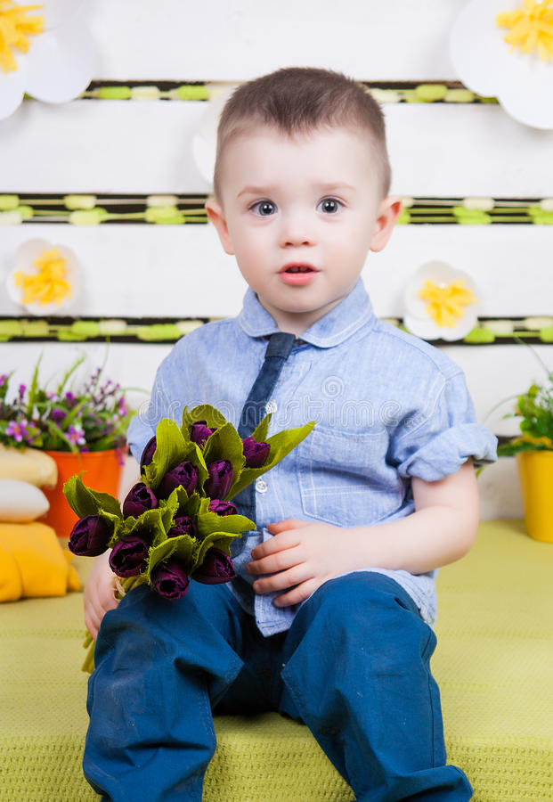 Cute boy in a blue denim shirt and tie, jeans and boots royalty free stock photo