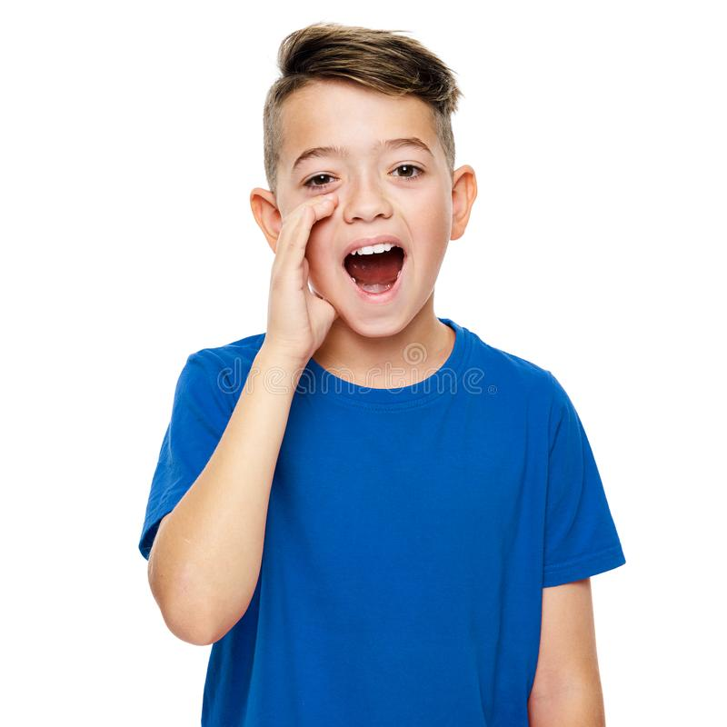 Cute boy in blue T-shirt shouting. Speech therapy concept over white background. Front view. royalty free stock photo