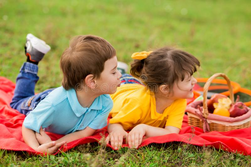 Cute boy in blue t-shirt wants to kiss girl with bangs in yellow t-shirt. Children lie on a blanket on the grass. The boy pursed. His lips, and the girl turned royalty free stock photo