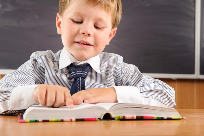 Download Cute Boy With Books At The Desk Stock Image - Image: 26124875