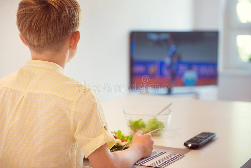 Cute boy child eating in kitchen and watching football royalty free stock photography